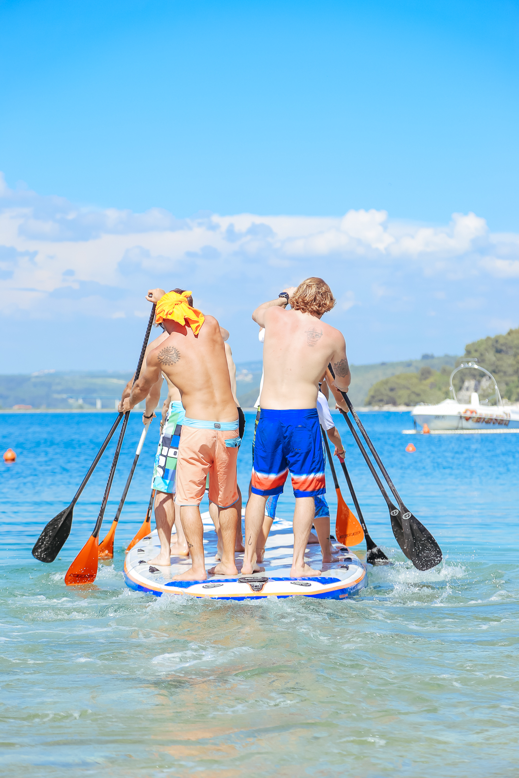 Stand Up Paddle team paddling on the beach